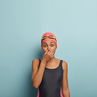 Active female swimmer posing with goggles