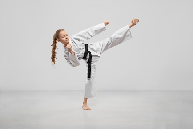 Active female teenager practising karate in studio