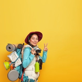 Active female traveler makes peace gesture, holds retro camera for taking pics, carries big rucksack with destination map, karemat and other tourist things