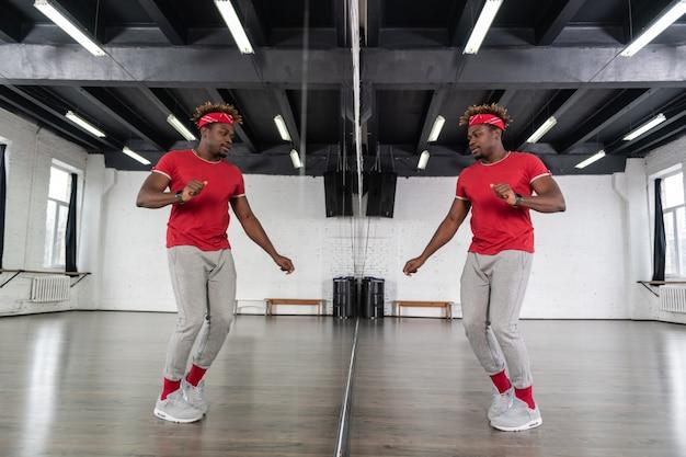 スタジオで繰り返しながら鏡の前で踊るスポーツ衣装のアクティブフィット男 Premium写真