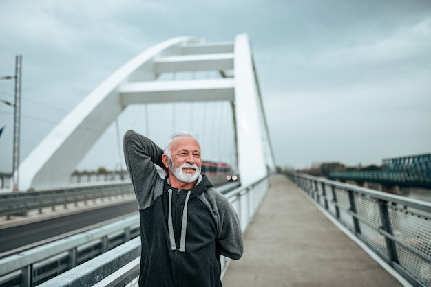 Active fit senior man stretching on the bridge in the city.