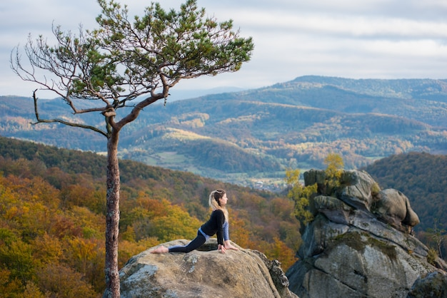 Active fit woman is practicing yoga on the top of the mountain near big tree