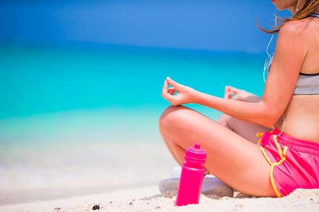 Active fit young woman in yoga position at her sportswear during beach vacation