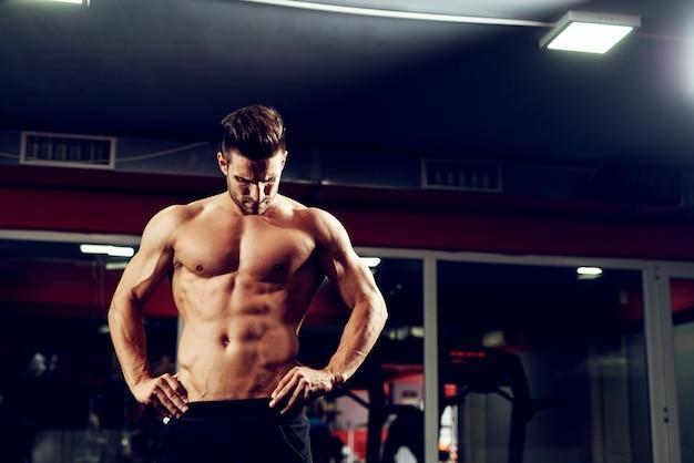 Активный фитнес человек стоит в тренажерном зале.