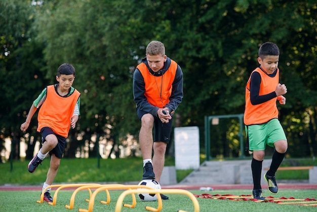 Active footballers train together on soccer field and follow the instructions of professional coach.