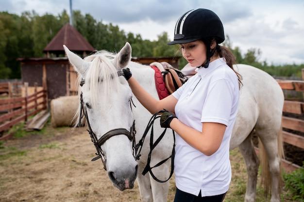 馬術用ヘルメットと白いポロシャツでアクティブな女の子と彼女の競走馬が田舎の環境でフィールドを下って移動