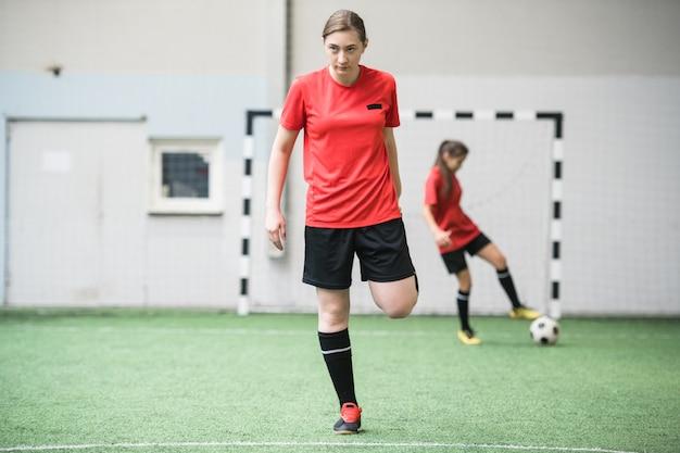ゲームの前にサッカー場で運動するスポーツユニフォームのアクティブな女の子