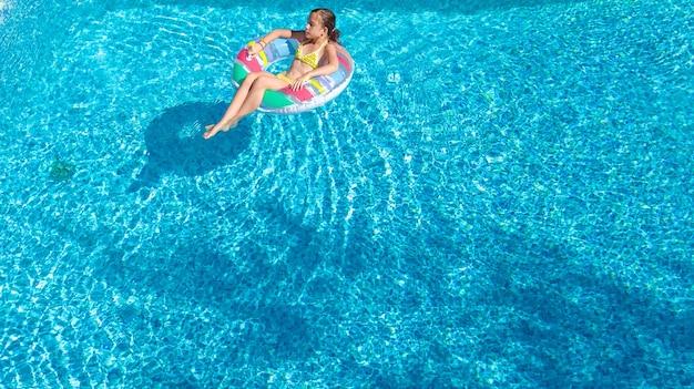 上からスイミングプールの空中上面でアクティブな女の子、子供はインフレータブルリングドーナツで泳ぐ、子供は青い水で楽しい