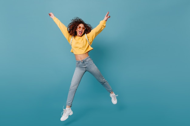 Active girl shows tongue. woman in yellow sweater and jeans happily jumping on isolated blue space.