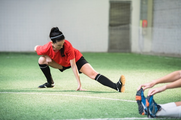 Active girl in sports uniform doing exercise for stretching legs on football field while working out before game