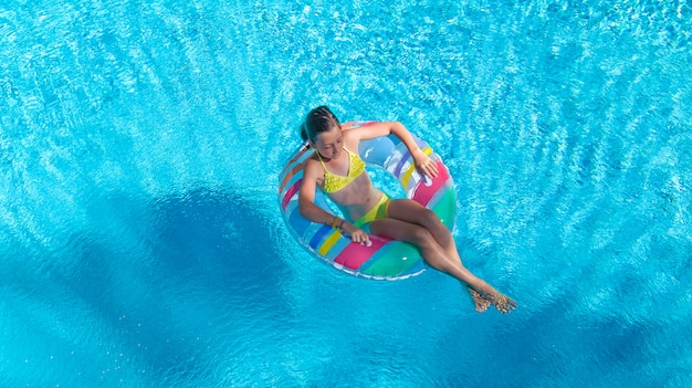 Active girl in swimming pool aerial top view from above, kid swims on inflatable ring donut, child has fun in blue water on family vacation resort