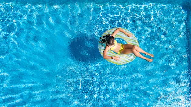 Active girl in swimming pool aerial top view from above, kid swims on inflatable ring donut