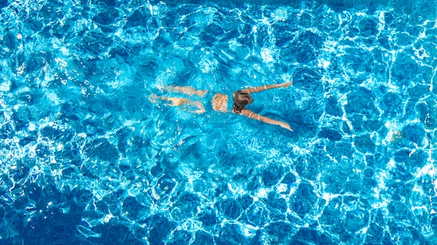 Active girl in swimming pool aerial view from above, young woman swims in blue water, tropical vacation, holiday on resort concept