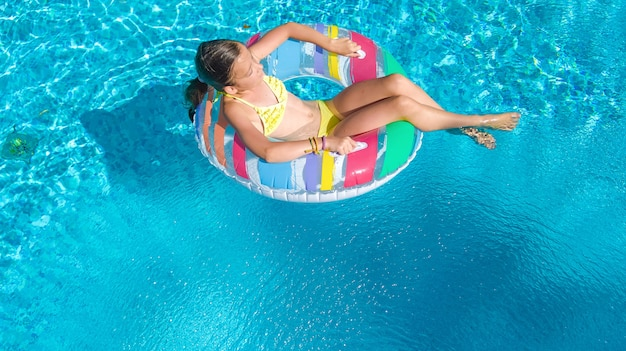Active girl in swimming pool aerial view, kid swims on inflatable ring
