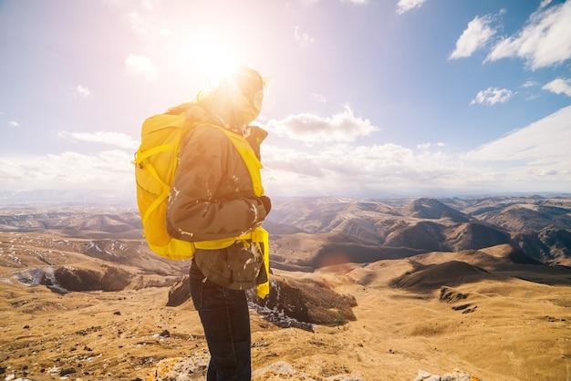 アクティブな女の子は黄色のバックパックでコーカサス山脈を旅し、太陽を楽しんでいます
