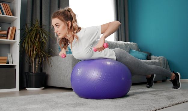 自宅での胃のトレーニングでフィットネスボールの上に横たわっている肘で曲がった腕のダンベルを持つアクティブな女の子