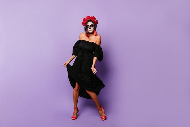 라일락 벽에 멕시코 두개골 춤의 메이크업 활성 소녀. 빨간 액세서리와 장미를 가진 숙녀가 전체 길이 사진을 위해 포즈를 취합니다.