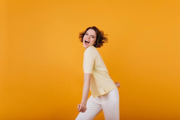 Активная девушка со стильной стрижкой танцует на ярко-оранжевой стене. очаровательная кудрявая дама в светло-желтой футболке веселится в помещении.