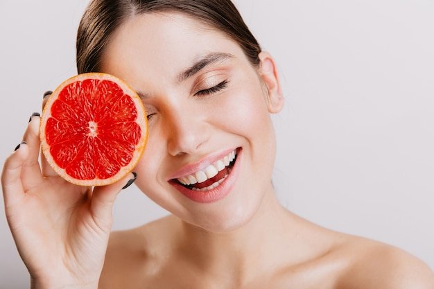 Active girl without makeup posing with grapefruit, bringing energy. portrait of brunette with snow-white smile on isolated wall.