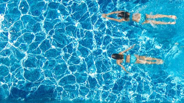 Active girls in swimming pool water aerial drone view from above, children swim, kids have fun on tropical family vacation, holiday resort concept