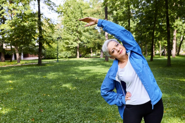 활성 회색 머리 수석 백인 아가씨 허리에 한 손을 잡고 공원에서 측면 굴곡을하는 동안 팔을 들고, 심장 운동 전에 몸을 워밍업, 행복 즐거운 표정을 갖는