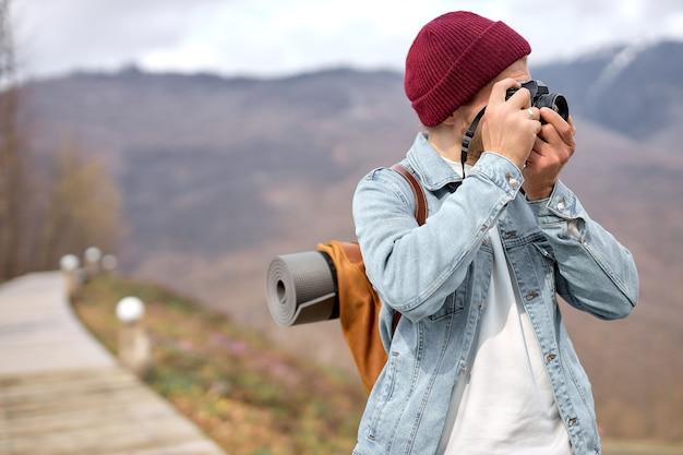 アクティブなハンサムな写真家の男が歩いている、旅行中にキャマーで写真を撮る