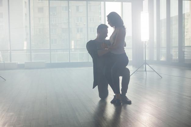 ダンスルームでキゾンバを踊るアクティブな幸せな大人。ダンサーのシルエット。熟練したダンサー。