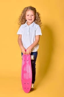 Active and happy girl with curly hair, headphones having fun with penny board, smiling face stand skateboard