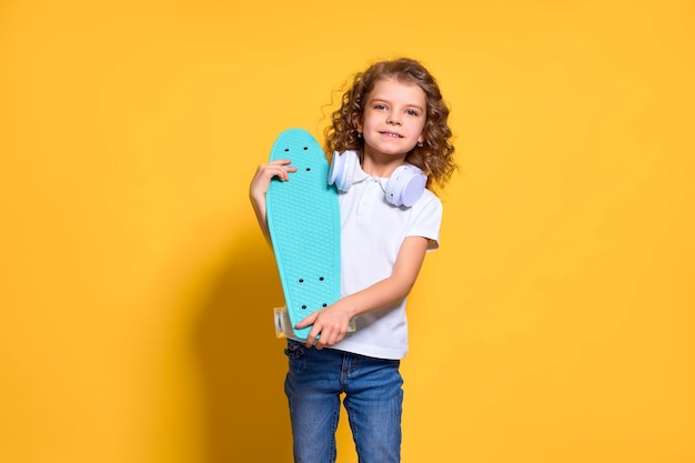 Active and happy kid having fun with penny board, smiling face stand skateboard
