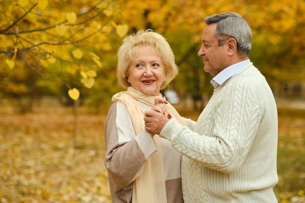 Active happy seniors dancing in autumn park