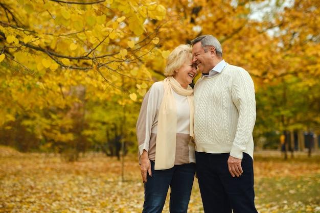 Active happy seniors walking in autumn park