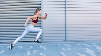 Active healthy female runner jogging in front of shutter