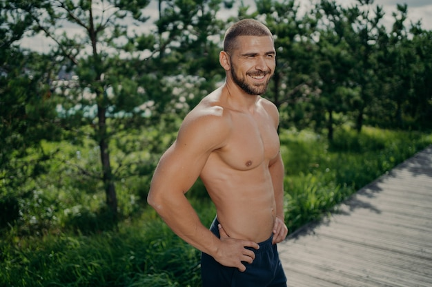 Active healthy lifestyle concept. cheerful sporty man works out in nature, enjoys athlete exercising, keeps hands on hips, has muscular body, looks somewhere with cheerful smile does morning gymnastic