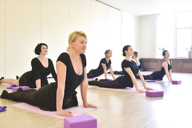 アクティブで健康的なライフスタイル、趣味、レクリエーション、幸福、減量の概念。白いスポーツホールでの授業中に柔軟性を高めるためにストレッチ体操でウォーミングアップするグループダンサーの女の子