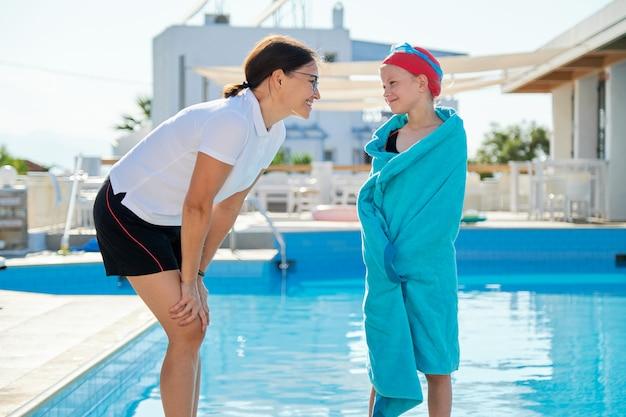 Активный здоровый образ жизни у детей. женщина-тренер разговаривает с девочкой возле открытого бассейна