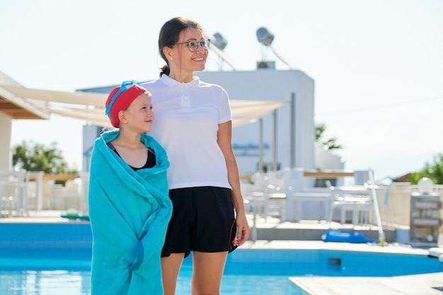 Active healthy lifestyle, mother and daughter child in sport hat goggles for swimming with towel near the outdoor pool