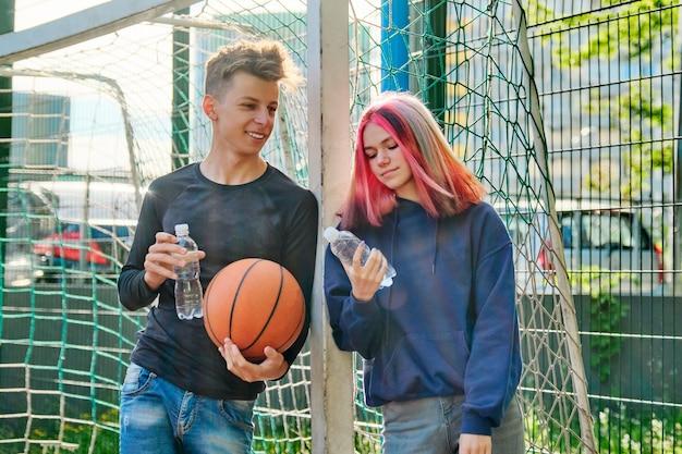 Активный здоровый образ жизни подростков 16, 17 лет в городе. пара с модными прическами на спортивной баскетбольной площадке разговаривает, стоит с мячом и бутылкой воды