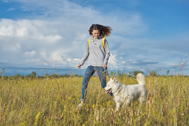 Active healthy lifestyle, teen girl running with white husky dog