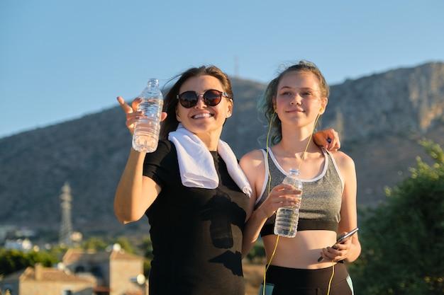 Активный здоровый образ жизни, две женщины, мать и дочь-подросток в спортивной одежде, разговаривают и пьют воду после тренировки, горный фон, закат