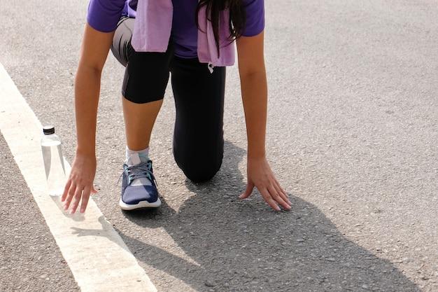 ランニングシューズを結ぶアクティブな健康な女性、ジョギングランナーのヘルスケアと幸福の概念。