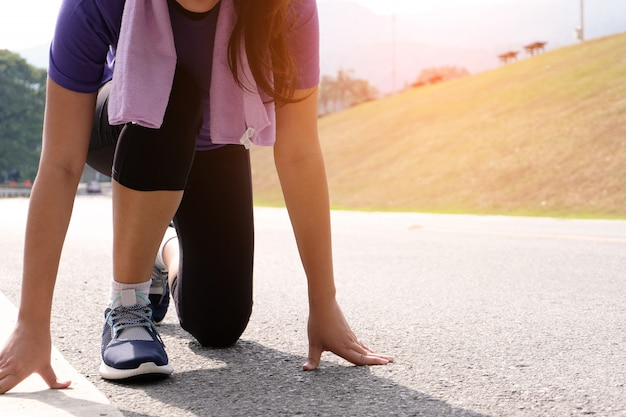 Active healthy woman tying running shoes,  jogging runner healthcare and well being concept.