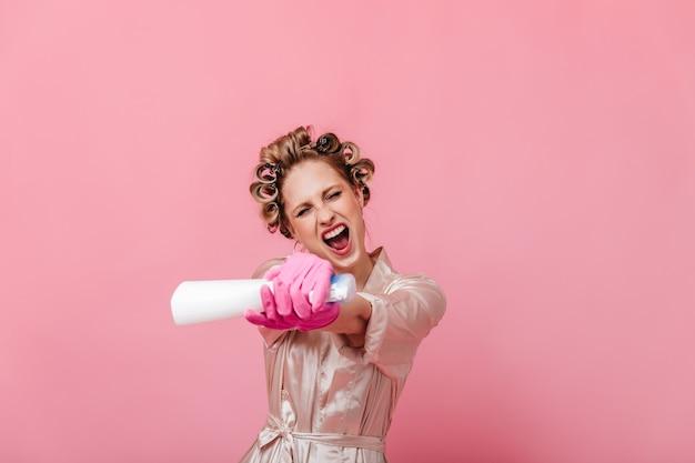 La casalinga attiva in veste di seta spruzza detergente per vetri