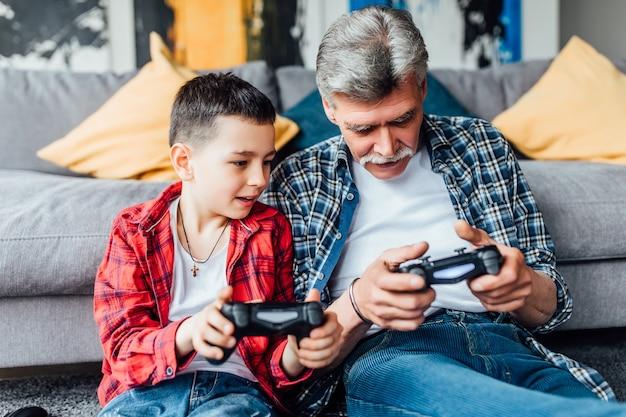 新しいビデオゲームを楽しんでいるアクティブなインスピレーションを得た男と彼の孫。
