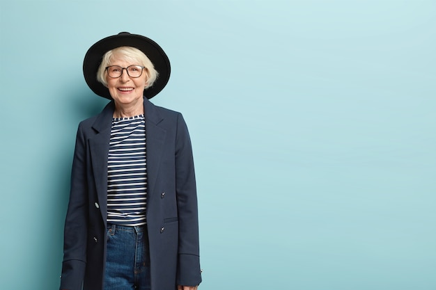 Active joyful stylish female teacher retires, wears hat and formal jacket, glad receiving congratulation from colleagues