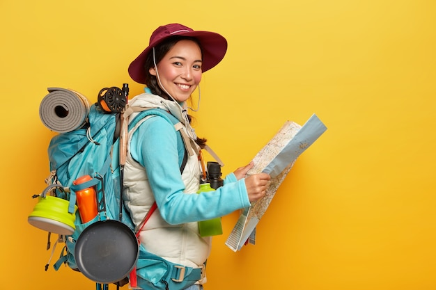 Active korean female tourist carries big rucksack, wears hat and casual clothes, holds map, studies route, has much things needed during traveling