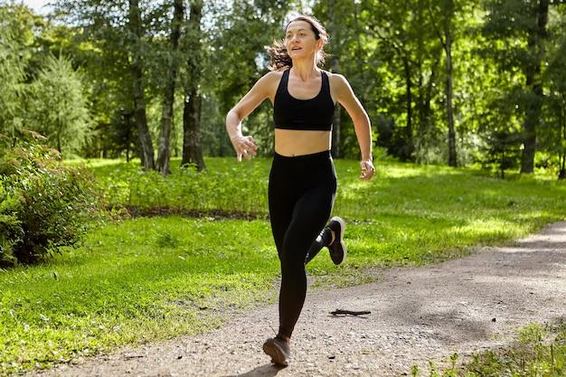44 세의 활동적인 여성이 낮에는 운동복을 입고 야외에서 달리고 있습니다.