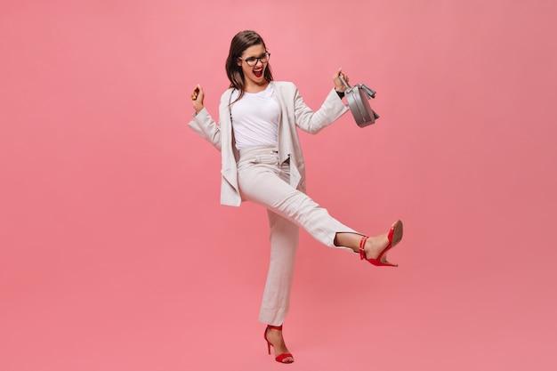 Активная дама в костюме позирует с сумочкой на розовом фоне. эмоциональная молодая женщина с удовольствием перед камерой в красных высоких каблуках.