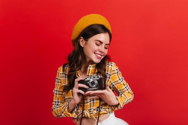 アクティブな女性は赤い壁に笑顔でかわいいです。ブルネットの女性はレトロなカメラで写真を撮ります。