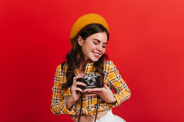 Active lady is cute smiling on red wall. brunette woman takes photo on retro camera.