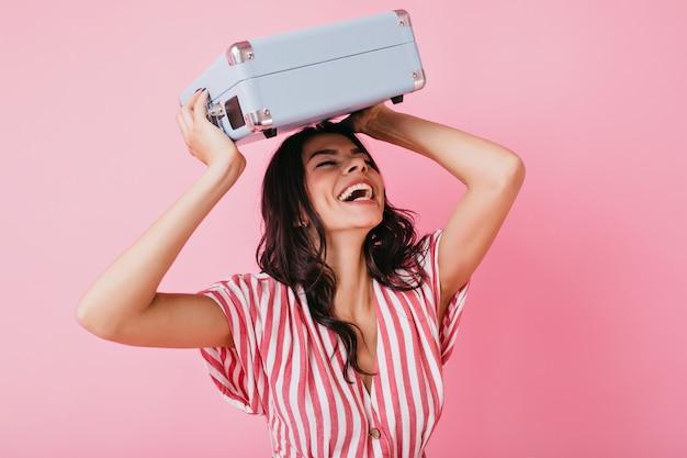 어두운 컬을 가진 활동적인 여성이 진심으로 웃습니다. v 넥 티셔츠를 입은 소녀가 가방을 머리 위로 올렸습니다.